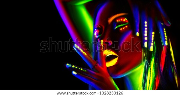 Disco dancer in neon light. Fashion model woman in neon light, portrait of beautiful model girl with fluorescent make-up, Body Art design in UV, painted face, colorful make up, over black background