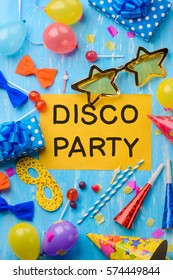 Disco party text on a yellow paper. Masquerade mask, balloons, confetti, handcrafted paper bows, lollipops, cocktail straws, a party hat on a blue background. A creative invitation.