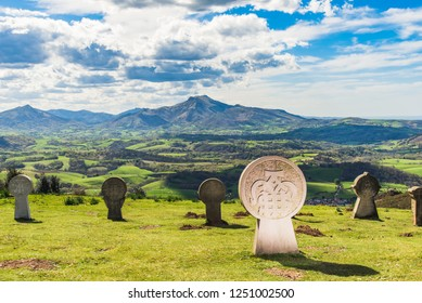 Discoidal stele in the village of Ainhoa with view on the mountains. Basque country of France.