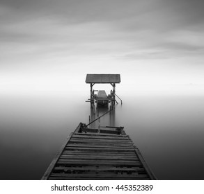 disconnected - A abandoned jetty on a beach in black and white. A slow shutter speed was used to see the movement of the clouds in the sky. (fine art)