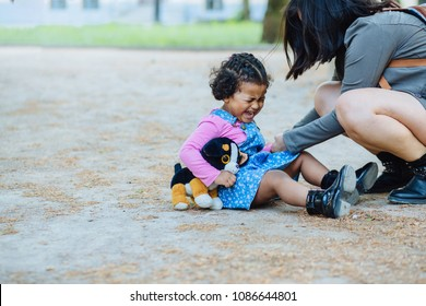Disconsolate hispanic toddler girl three years old crying while sit on the ground outdoor. Her ecuadorian mother try to calm down on the city street.