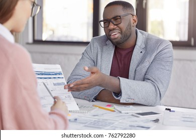 Discontent black male company owner points at documents which his secretary holds, has unhappy look as can`t understand something, disappointed with mistakes in accounting, being sad and frustrated