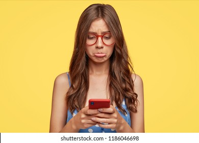 Discontent Caucasian woman has offensive expression, purses lower lips in displeasure, uses modern mobile phone, types text message, connected to wireless internet poses against yellow background