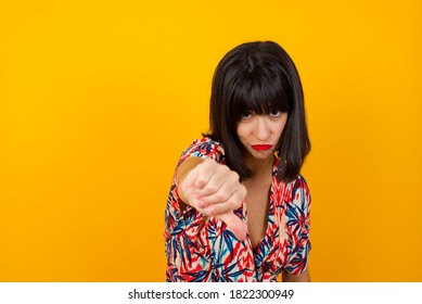 Discontent European woman shows disapproval sign, keeps thumb down, expresses dislike, frowns face in discontent, dressed in white shirt, isolated over yellow background. Body language concept.