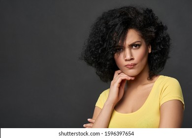 Discontent frowning woman looking at camera, over gray studio background