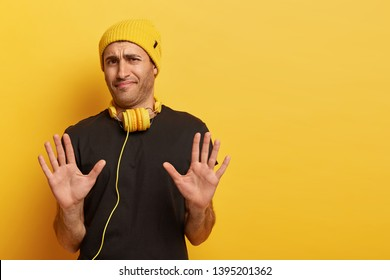 Discontent unshaven handsome guy looks with apathy, demonstrates refusal gesture, sees something disgusting, says its not for me, wears stylish hat in one color with headphones, refuses action