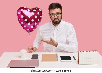 Discontent unshaven man demonstrates valentine or balloon, has unhappy expression, wears spectacles and shirt, being perfectionist, isolated over pink background, doesnt like recieved present