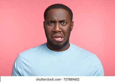 Discontent young African American male curves lips, dislikes what he sees, displeased with bad news, has disgust towards something, isolated over pink background. Negative human emotions concept.