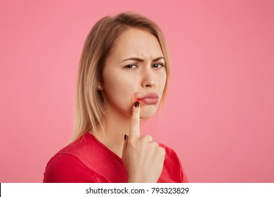 Discontent young beautiful female with unhappy look, has oral herpes, indicates at wound near lips, stands sideways against pink background. People, skin care and health problems concept.