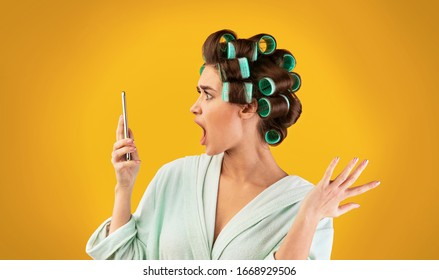 Discontented Housewife Holding Smartphone Reading Message Or Shocking News Standing Over Yellow Studio Background.