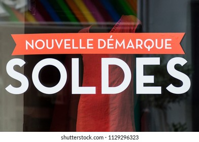"""discount sign """"SOLDES nouvelle demarque"""" in french,  the traduction of  (sales, new markdown) on window in french fashion store showroom on summer clothes background"""