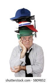 A discouraged businessman or academic wearing too many hats.  Isolated on white.