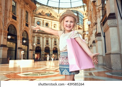 Discover most unexpected trends in Milan. Portrait of happy fashion girl with pink shopping bag in Galleria Vittorio Emanuele II rejoicing