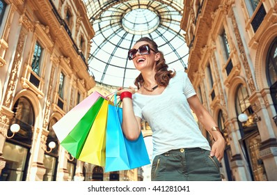 Discover most unexpected trends in Milan. Smiling fashion monger in eyeglasses with colorful shopping bags in Galleria Vittorio Emanuele II looking into the distance