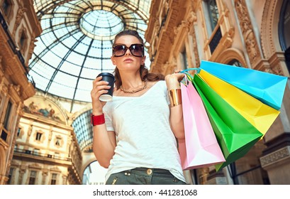 Discover most unexpected trends in Milan. Fashion woman in eyeglasses with colorful shopping bags and coffee cup in Galleria Vittorio Emanuele II