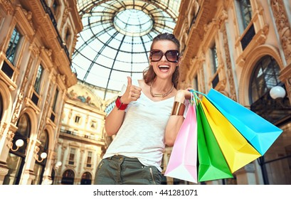 Discover most unexpected trends in Milan. Portrait of happy fashion woman in eyeglasses with colorful shopping bags in Galleria Vittorio Emanuele II showing thumbs up