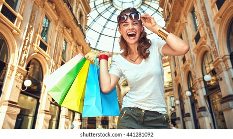 Discover most unexpected trends in Milan. Portrait of smiling fashion woman with eyeglasses and colorful shopping bags in Galleria Vittorio Emanuele II