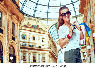 Discover most unexpected trends in Milan. Full length portrait of smiling fashion woman in eyeglasses with colorful shopping bags and coffee cup in Galleria Vittorio Emanuele II