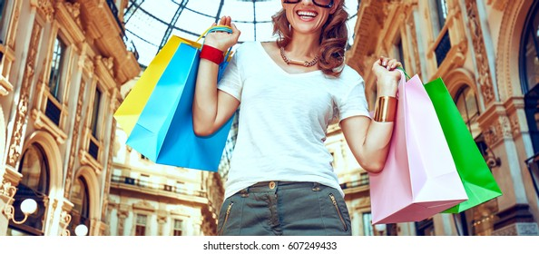 Discover most unexpected trends in Milan. Happy fashion woman with colorful shopping bags in Galleria Vittorio Emanuele II