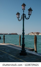 Discover old and crowded Venice differently. Original lantern post with light pink glass in one of many waterfronts in Guidecca island.