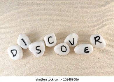 Discover word on group of stones with sand as background