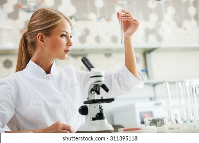 Discovering cure. Concentrated young female scientist holding test tube and looking at it while sitting at her working place