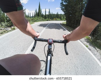 Discovering Tuscany on a racing bicycle. Young adult man enjoying a ride on a bicycle on a sunny spring day.
