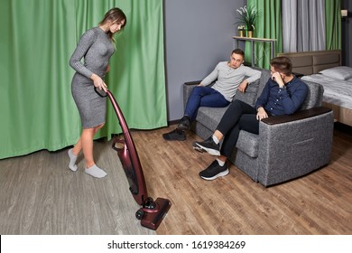 Discrimination of women, sexism in the family. A man communicates with a friend sitting on a sofa while his wife tidies up the room.
