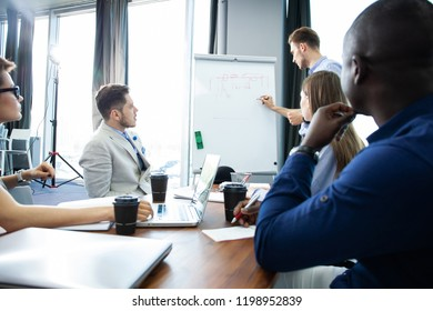 Discussing company progress. Confident young man standing near whiteboard and pointing graph while his colleagues sitting at the desk