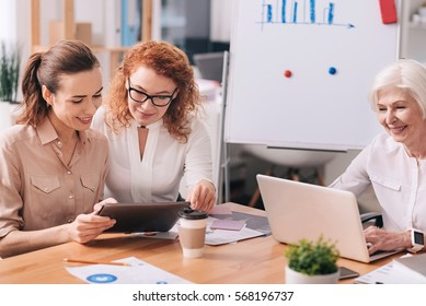 Discussing the current project. Smiling concentrated involved businesswomen sitting in the office in front of the white board and having conversation while using modern gadgets