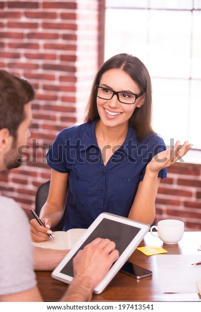 Discussing new creative project. Two cheerful business people in casual wear talking and gesturing while sitting face to face at the table