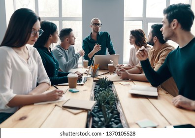 Discussing risky ideas. Group of young modern people in smart casual wear discussing something while working in the creative office