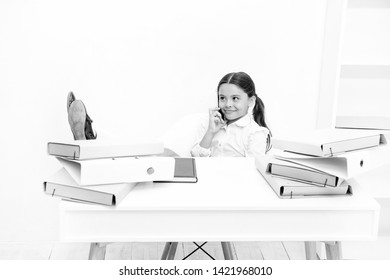 Discussing rumors. Cute gossip girl. Schoolgirl smiling face discuss fresh gossips with mates. Child use smartphone mobile to communicate in school. Fresh school gossip. She like talking too much.
