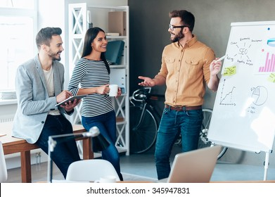 Discussing some new project together. Confident young man standing near whiteboard and pointing it with smile while his colleagues standing near him