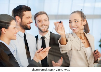 Discussing successful business project. Confident young businesswoman drawing a graph on glass and smiling while her colleagues standing near her