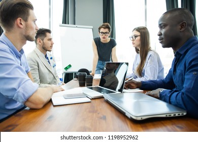 Discussing successful project. Group of young cheerful business people working and communicating while sitting at the office desk together with colleagues sitting in the background
