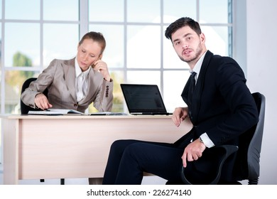 Discussion of business problems. Two businessman sitting at the table until one man businessman looking at the camera.