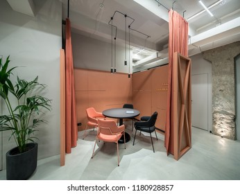 Discussion zone with orange curtains in a luminous office with gray walls and concrete column. There is a black round table with a laptop, multicolor chairs, partition, plant in a pot, hanging lamps.