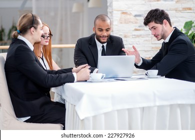 Discussions partners business over a cup of coffee and a laptop. Four smiling successful businessmen sitting at table in office while discussing their business doings. Young men dressed in formal wear