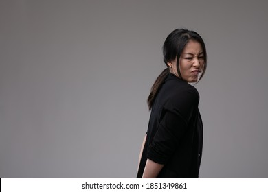 Disdainful Asian woman showing her disgust or dislike turning away with a grimace over a grey studio background with copyspace