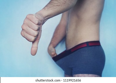 diseases in the urogenital sphere of men.. man shows his thumb that he has a small penis. The concept of impotence. Impotent looks at his cock