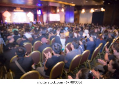 Disfocus of speakers on the stage under the color full of downlight with Rear view of Audience in the conference hall or seminar meeting, business and education concept