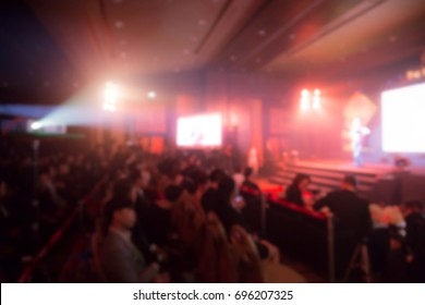 Disfocus of two speakers on the stage with Rear view of Audience in the conference hall or seminar meeting, business and education concept