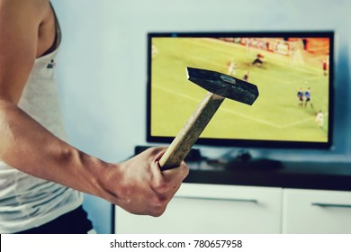 A disgruntled fan is disappointed by the loss of their favorite team. man wants to break the TV. The guy swung a hammer at the screen. Emotional fans watching the football