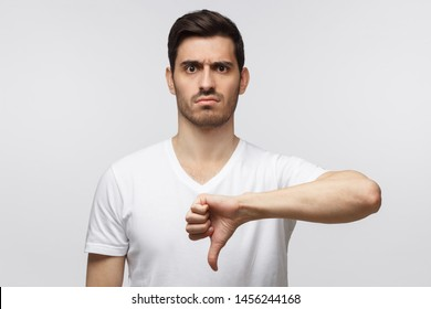 Disgruntled grumpy dissatisfied annoyed unhappy young man showing thumb down as dislike gesture isolated on gray background