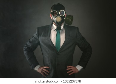Disgruntled man in a gas mask and suit on a gray background. Pollution of environment concept.