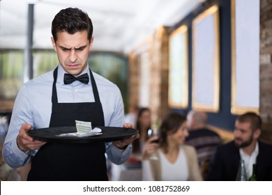 disgruntled waiter holding serving tray in restaurant with tips