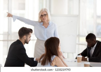 Disgruntled young employee intern ignoring mature angry executive firing incompetent worker asking to leave group office meeting, different age generations conflict, discrimination at work concept