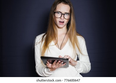 disgruntled young girl with glasses holds a tablet in her hands