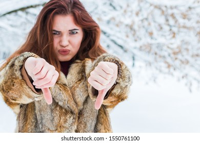 """disgruntled young woman shows a """"bad"""" gesture with her hands. young girl in winter forest"""